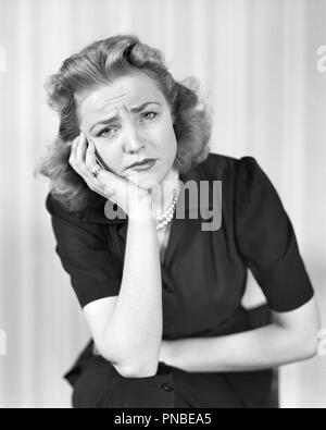 1940s WOMAN LOOKING AT CAMERA WITH A SAD DISGRUNTLED PAINED SICK FACIAL EXPRESSION - a2730 HAR001 HARS PERSONS AILMENT HEADACHE EXPRESSIONS B&W SADNESS EYE CONTACT BRUNETTE SUFFERING DISCOVERY DISGUST TOOTHACHE NAUSEA POOR HEALTH AILING DISAPPOINTED DISGRUNTLED MID-ADULT MID-ADULT WOMAN MISERABLE ACHE BLACK AND WHITE CAUCASIAN ETHNICITY DISLIKE HAR001 OLD FASHIONED - Stock Image