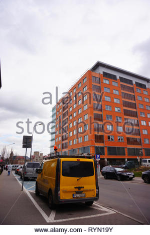 Poznan, Poland - March 8, 2019: Yellow technical service bus wrongly parked close by the Globis office building in the city center. - Stock Image