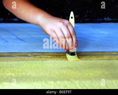 An overhead shot of a child painting a mural. - Stock Image