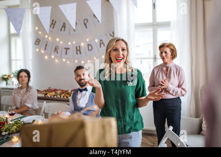 Happy surprised young woman receiving a gift on indoor party. - Stock Image