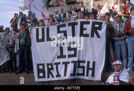 Ulster football fans in Trafalgar Square after a win with flags and a banner reading Ulster is British - Stock Image