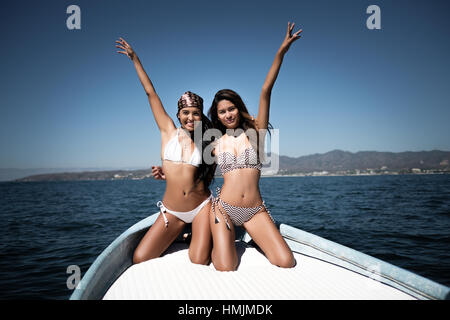 2 young attractive hispanic women in bikini posing for a photo on a boat - Stock Image