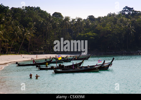 Holidaymakers swimming in clear water of the Andaman Sea at Freedom Beach and longtailboats anchored in bay. - Stock Image