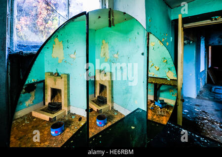 Mirror reflects a fireplace in the bedroom of an abandoned Irish Farmhouse. - Stock Image