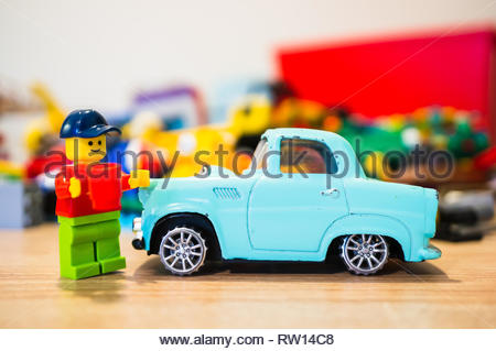 Poznan, Poland - February 15, 2019: Lego man with hat standing next to his classic parked car. He is the proud owner. - Stock Image