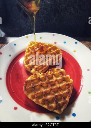 Valentine's Day breakfast treat, heart shaped waffles with syrup - Stock Image