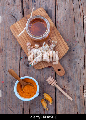 Alternative skin care - Homemade scrubs curcumin powder,honey and curcumin roots set up on old wooden table. - Stock Image
