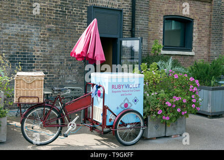 Ruby Violet Ice Cream bicycle with red sunshade next to planters in front of shop Kings Cross London England Britain UK - Stock Image