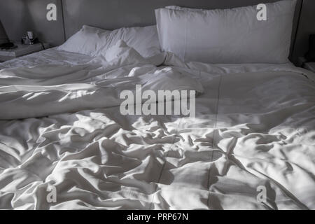 Bed With Slept In Sheets Morning Sunlight - Stock Image