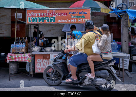 Thailand family of mother, father and child riding a motorcycle for collecting food from a street food stall. Southeast Asia - Stock Image