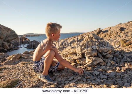 boy playing with rocks - Stock Image