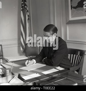 1960s, US Ambassor to NATO at his desk going through paperwork. - Stock Image