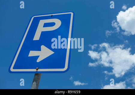 Parking sign against a blue sky and white clouds. - Stock Image