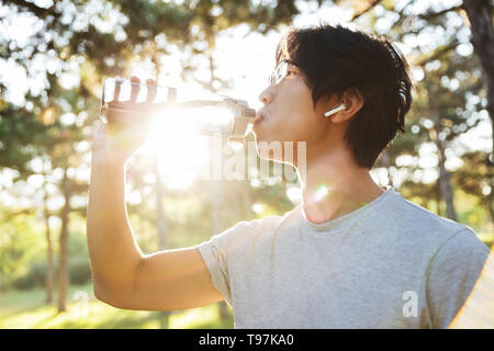 Side view of a young asian sportsman wearing earphones, drinking water while standing at the park - Stock Image