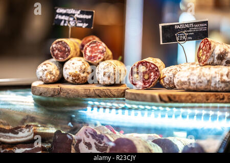 Various types of Dried organic salami sausage and saucisson on wooden cutting board in a store market - Stock Image
