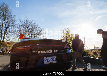 VANCOUVER, BC, CANADA - APR 20, 2019: 420 festival goers walk past a VPD car in English Bay, Vancouver. - Stock Image