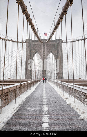 Couple walking over Brooklyn Bridge at heawy snow storm - Stock Image