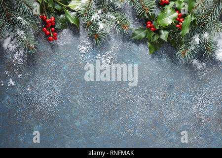 Christmas background with fir tree and holly berry on a blue stone background covered in snow with copy space. - Stock Image