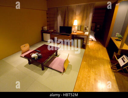 Traditional Japanese style hotel room with tatami mats and futon bed. - Stock Image