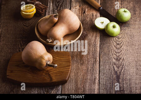 Raw fresh pumpkin, cooking ingredients, autumn traditional vegetable dish preparation, rural wooden table, close up, selective focus - Stock Image