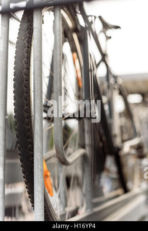 Single commuter mountain bike parked in a bicycle rack at a train station - Stock Image