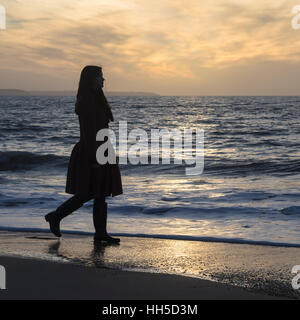 a woman is walking along the beach during sunset - Stock Image