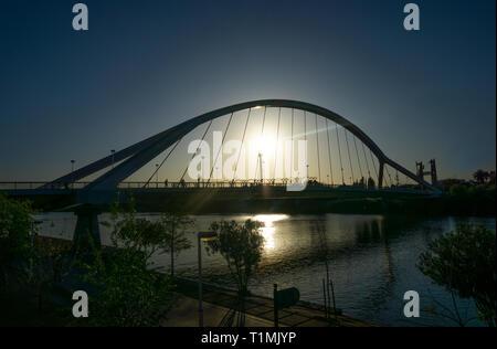 The Puente de la Barqueta on the Guadalquivir River in Seville at sunset - Stock Image