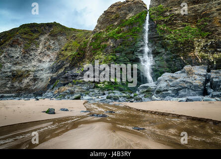 Waterfall of the River Saith flows over cliffs on the beach at Tresaith Bay, a coastal village in Ceredigion, Wales. - Stock Image