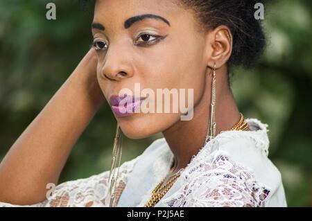 Close-up of beautiful face of pretty woman posing near a foliage. - Stock Image