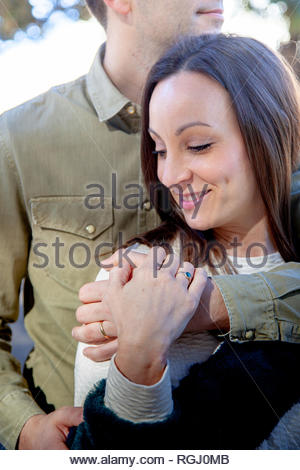 Man hugs his girl from behind in a public park - Stock Image