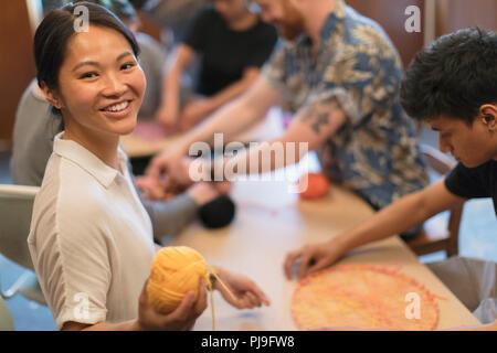 Portrait smiling woman doing string art project - Stock Image