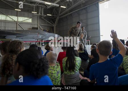 Staff Sgt. Cody Butler, 33rd Fighter Wing weapons lead crew chief, and Senior Airman Samill Harkness, 33 FW weapons lead crew member, answer questions from young tour participants on Mar. 14, 2019, at Eglin Air Force Base, Fla. Children from the base elementary school got the chance to tour the 33rd FW seeing the different careers of Airmen. - Stock Image