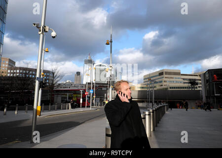 A man standing on the street near the Shard skyscraper talking on a mobile phone (cell phone) with a view of the City of London UK KATHY DEWITT - Stock Image