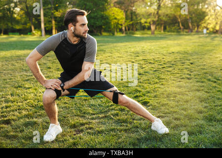 Portrait of athletic sporty man with fitness body stretching his body with expander equipment during workout in green park - Stock Image