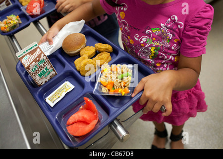 A student carries her tray in an elementary school lunch line. - Stock Image