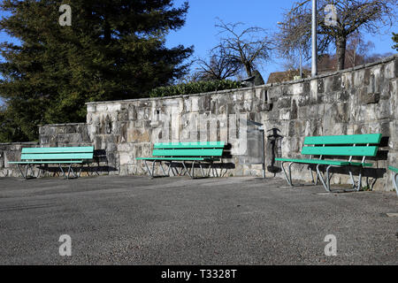 Green benches made of wood and concrete photographed on a sunny spring day in Nyon, Switzerland. In this photo you can also see asphalt walkway. - Stock Image