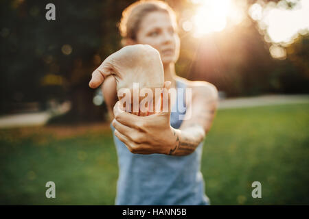 Young woman stretching hand muscles before workout. Fitness female stretching at the park. - Stock Image