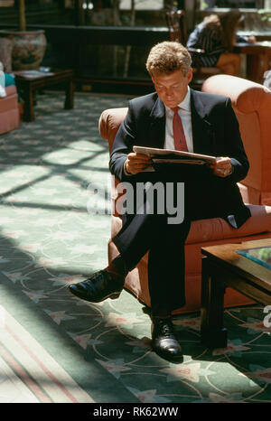 Businessman Reading a Newspaper in a Hotel Lobby, USA - Stock Image
