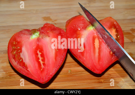 heart shaped red tomato  cut in two with huge knife - Stock Image