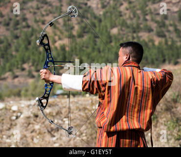 Archer wearing traditional Bhutanese dress practising archery (national sport) in the countryside Bhutan - Stock Image