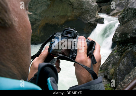 Photographer inspecting his image in front of waterfall in river laer, Norway - Stock Image