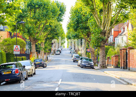 London, UK - September 15, 2018 - View of a treelined uphill street with a school children sign in West Hampstead - Stock Image