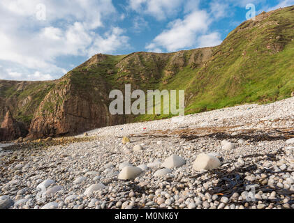 Cliff and shingle beach  in a cove at Bloody Foreland, at the north-west tip of County Donegal, Ireland - Stock Image