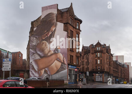 Glasgow - mural on side of tenement buildings of St Mungo, the patron saint and founder of Glasgow as a baby, Scotland, UK - Stock Image