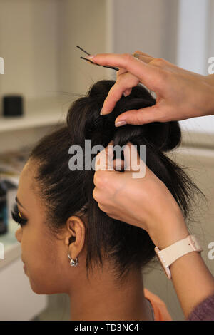 Hands of  professional female hairstylist make an evening hairstyle for her client. Hairdressing services. Creating hairstyles. Process of hair stylin - Stock Image