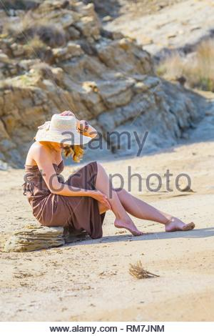 Barefeet on sandy beach sitting on stone - Stock Image