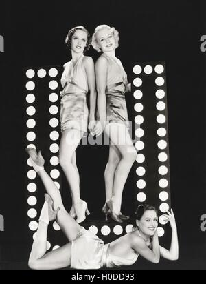 Three models posing by large letter U - Stock Image