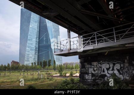 The modern architecture of European Central Bank building seen from underneath the Deutschherrnbrücke iron bridge, Frankfurt am Main, Hesse, Germany. - Stock Image