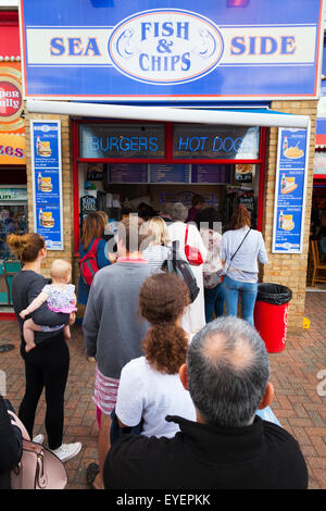 People queue for fish and chips at the seaside - Stock Image