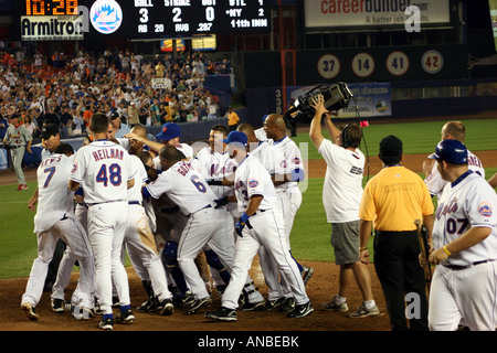The New York Mets mob teammate Shawn Green after his extra-inning game winning home run at Shea Stadium on June - Stock Image